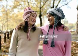 Two women wearing sweaters